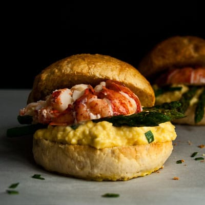 An amazing Lobster Breakfast Sandwich piled high with creamy scrambled eggs, asparagus and lobster on a fresh brioche sandwich bun!