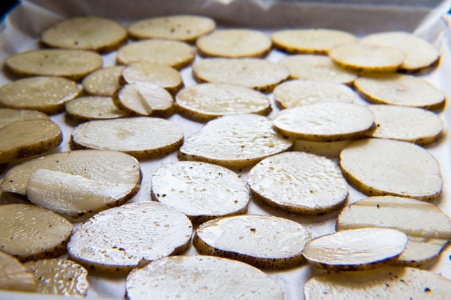 Sliced potatoes tossed in olive oil and seasoned for baking before making our Irish Nachos.