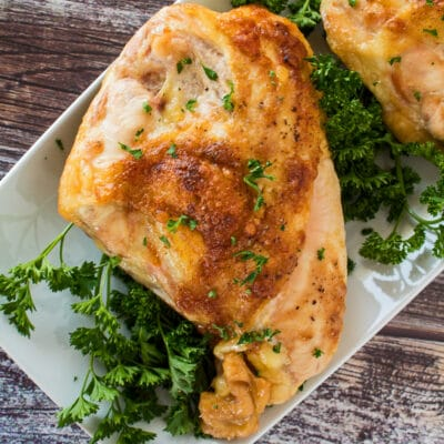 tender oven roasted bone in chicken breast garnished with fresh parsley on white plate
